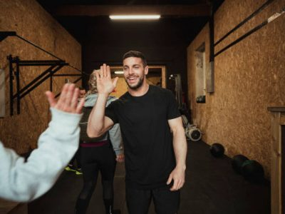 Unrecognisable person greeting the coach with a high-five at a gym gym.