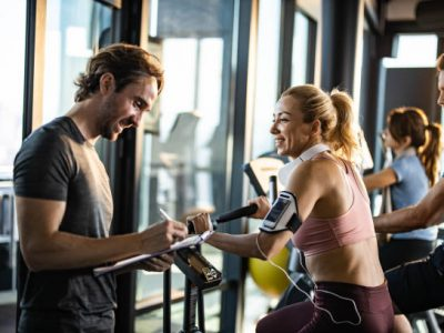 Happy woman exercising on stationary bike in a gym and looking at her coach making plans for her future sports trainings.