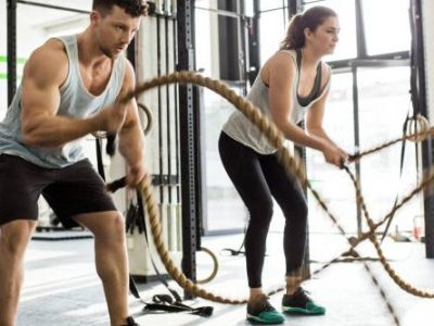 Muscular man and woman exercising with battle ropes at cross training gym