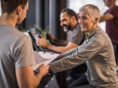 Happy mature woman having a sports training on exercise bike in a gym and talking to her fitness instructor.